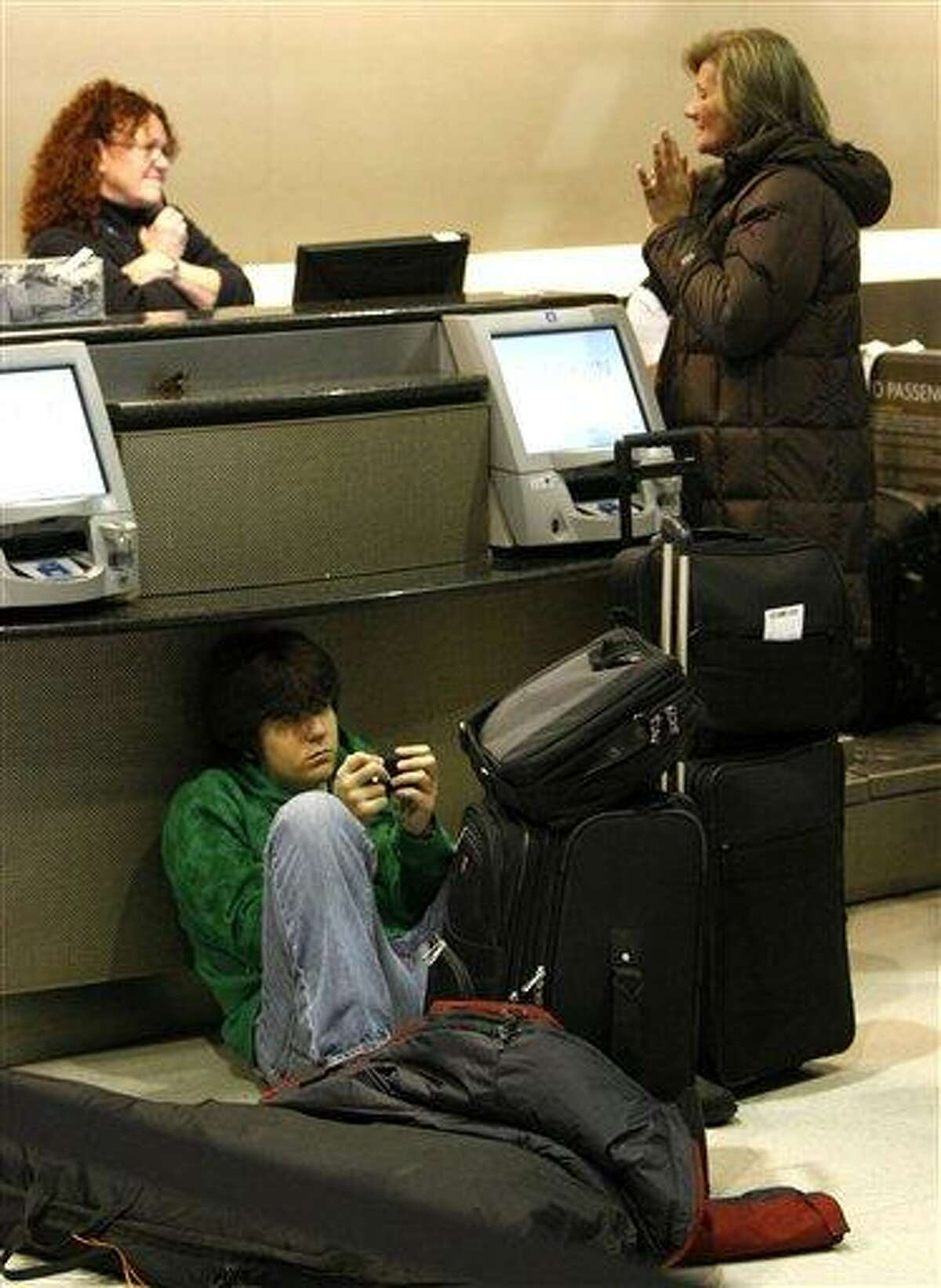 Daniel Larson sits on the floor as his mother Nancy, right, talks with a ticketing agent at the Delta Airlines counter in the Detroit Metropolitan Airport, Sunday, Dec. 27, 2009 in Romulas, Mich. The U.S. government tightened airline security as it searches for answers to how a 23-year-old Nigerian man eluded extensive systems intended to prevent attacks like his botched Christmas Day effort to blow up a Northwest flight from overseas. (AP Photo/Charles Rex Arbogast)