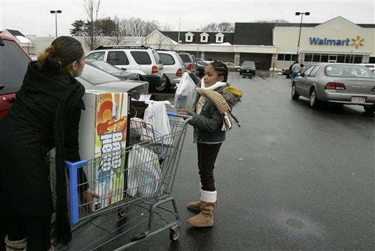 Delores Simmons, left, of Dorchester Mass., and her daughter Kaya, 10, unload their shopping cart at a Walmart in Framingham, Mass., Saturday Dec. 26, 2009. (AP Photo/Adam Hunger)