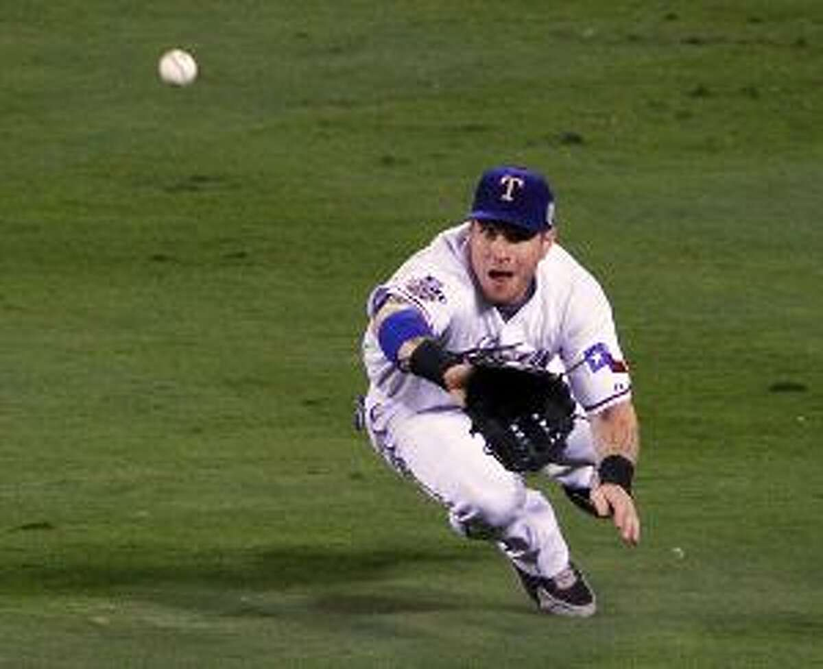 AP Texas Rangers center fielder Josh Hamilton dives to make a catch on fly ball by San Francisco Giant Nate Schierholtz to end the second inning of Game 4 of the World Series Sunday in Arlington, Texas. MLB Commissioner Bud Selig indicated Sunday that the league may expand the postseason, including adding more wild card teams.