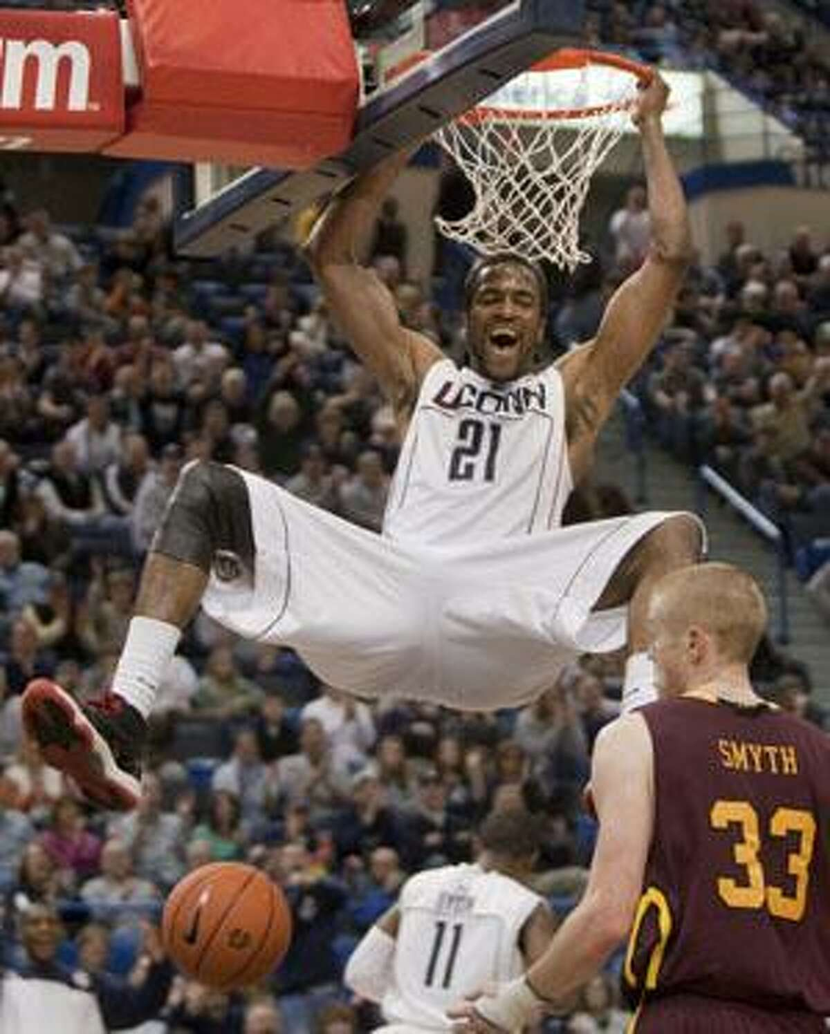 Connecticut's Stanley Robinson, top, dunks the ball while Iona's Kyle Smyth, right, looks on during the second half of Connecticut's 93-74 victory Sunday in Hartford.