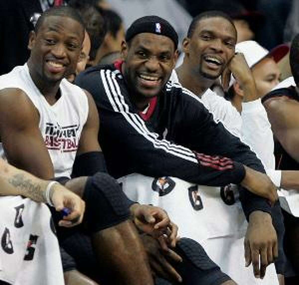 AP From left to right, Miami Heat players Dwyane Wade, LeBron James, and Chris Bosh laugh in the final moments of their game against the New Jersey Nets, Sunday, at the Prudential Center in Newark, N.J. The Heat defeated the Nets 101-78.