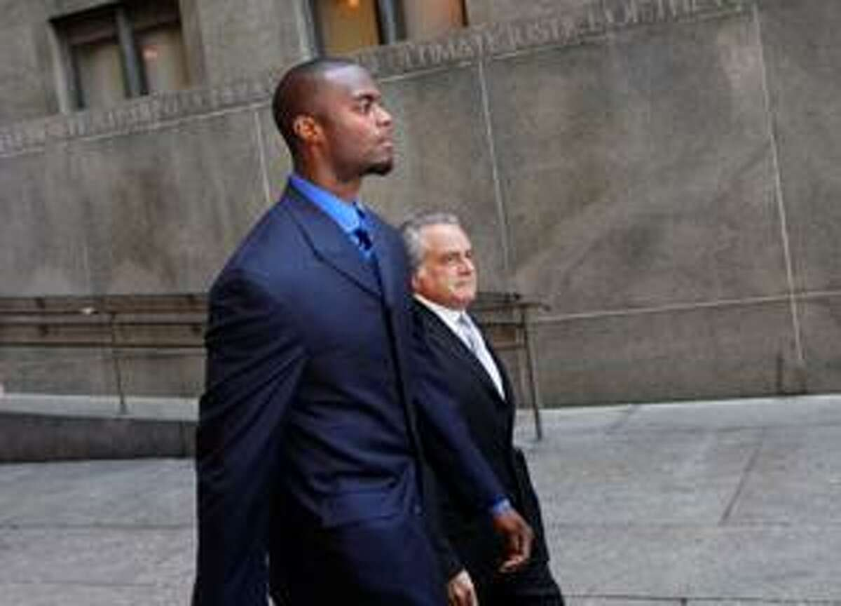 AP Former New York Giant Plaxico Burress, foreground, and his attorney Benjamin Brafman, leave Manhattan criminal court in New York, Thursday. Burress pleaded guilty to a weapons charge and agreed to a two-year prison term for accidentally shooting himself at a Manhattan nightclub.
