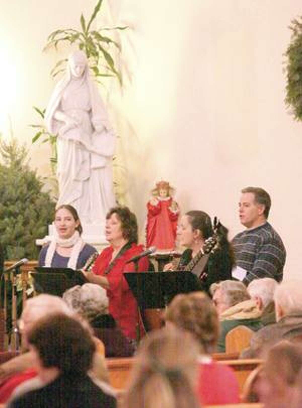 The St. Joseph Folk Choir sang during Christmas morning service Friday in Winsted.