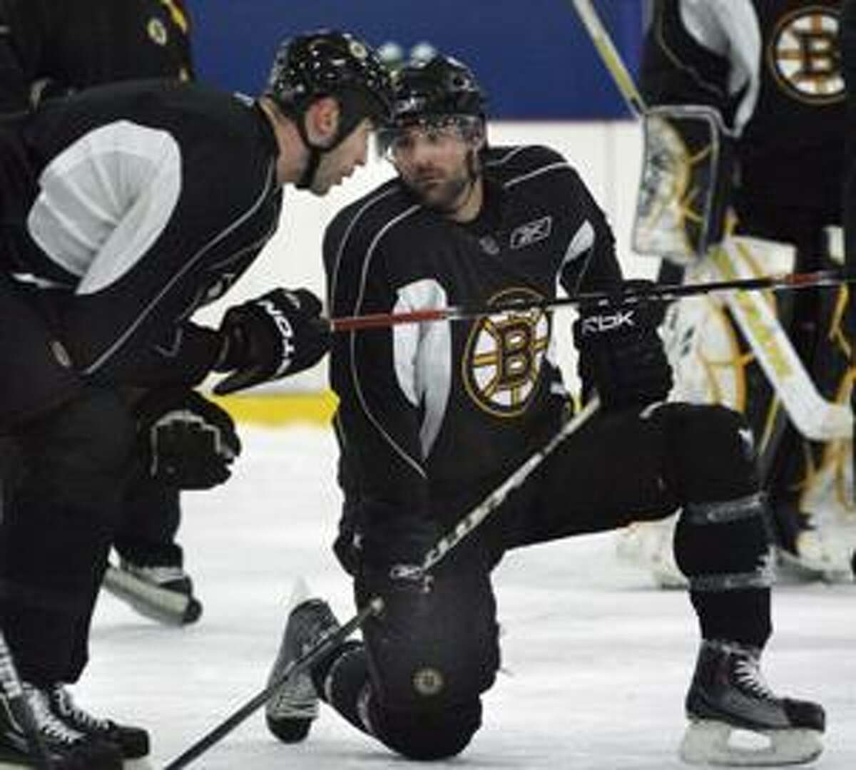 AP Boston Bruins captain Zdeno Chara, left, speaks with teammate Johnny Boychuk during practice in Wilmington, Mass. Thursday. The Bruins are preparing for their second-round NHL playoff series against the Philadelphia Flyers, which starts Saturday.
