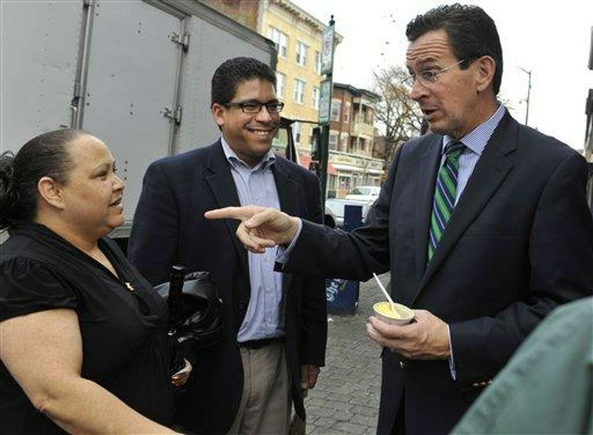 Connecticut Democratic gubernatorial candidate and former Stamford Mayor Dan Malloy, right, asks Milagros Vega of Hartford, left, to vote as State Rep. Kelvin Roldan, D-Hart., looks on, during a tour of the Parkville section of Hartford, Conn., Wednesday, Oct. 27, 2010. Malloy faces Republican Tom Foley in the Nov. 2 election. (AP Photo/Jessica Hill)