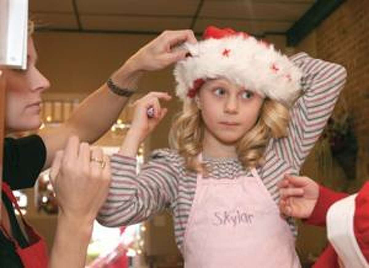 Liza DiMartino helps her daughter Skylar, 8 put on her Christmas hostess hat at Kelly's Kitchen in Winsted Christmas morning.