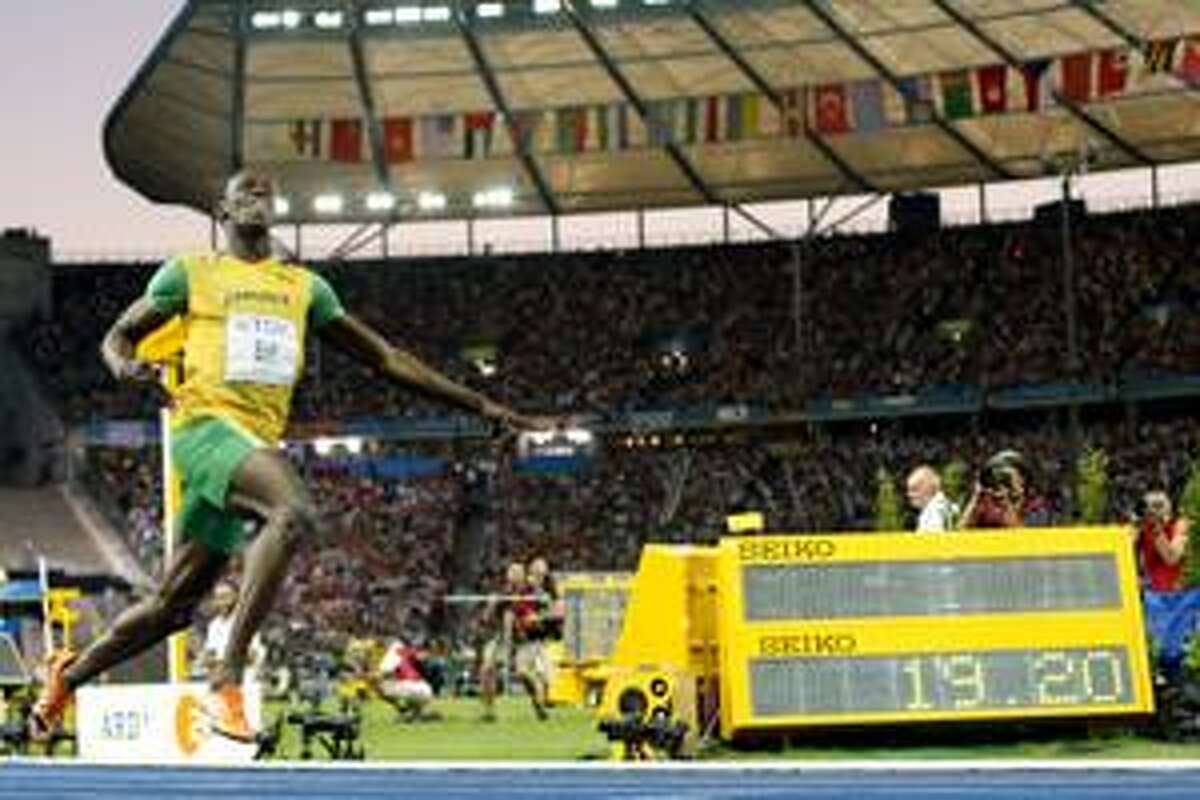 AP Jamaica's Usain Bolt runs past the timing board after setting a new world record as he wins the men's 200-meter final during the World Athletics Championships in Berlin on Thursday.
