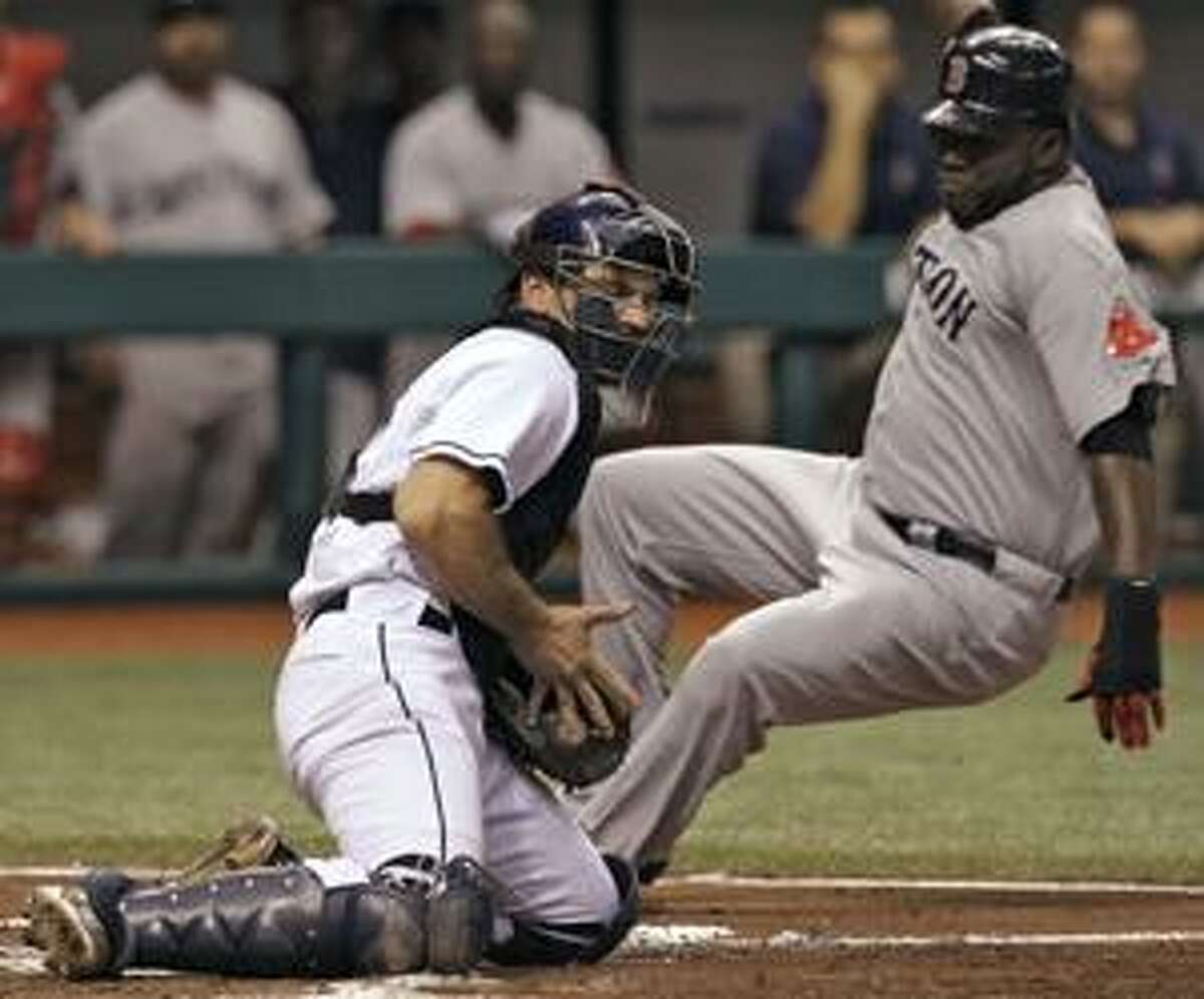 Boston Red Sox's David Ortiz, right, slides in ahead of the tag by Tampa Bay Rays catcher John Jaso during the third inning of a baseball game Monday, July 5, 2010, in St. Petersburg, Fla. Ortiz scored on a triple by teammate Kevin Youkilis. (AP Photo/Chris O'Meara)