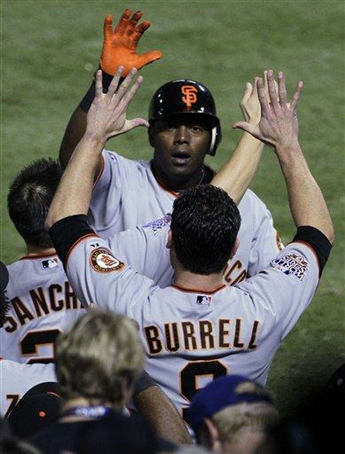 San Francisco Giants' Edgar Renteria, right, is congratulated by Pat Burrell after Renteria hit a three-run home run during the seventh inning of Game 5 of the World Series against the Texas Rangers Monday, in Arlington, Texas. (AP Photo/Tony Gutierrez)