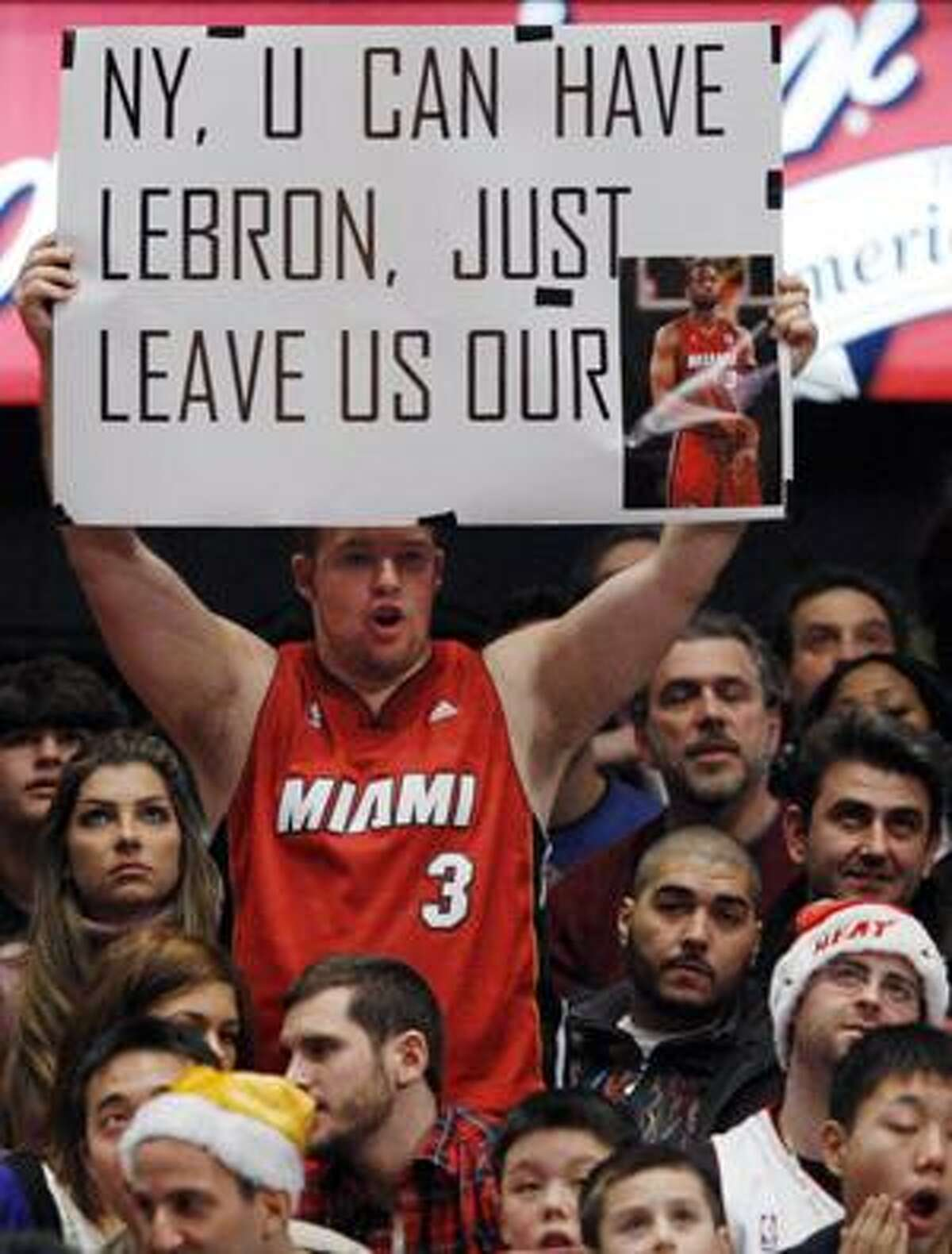 FILE - This Dec. 25, 2009, file photo shows a Miami Heat fan, dressed in a Dwyane Wade jersey, holding up a sign taunting the New York Knicks about their pursuit of LeBron James from the Cleveland Cavaliers while defending Wade in the Heat's 93-87 victory over the Knicks in an NBA basketball game at Madison Square Garden in New York.