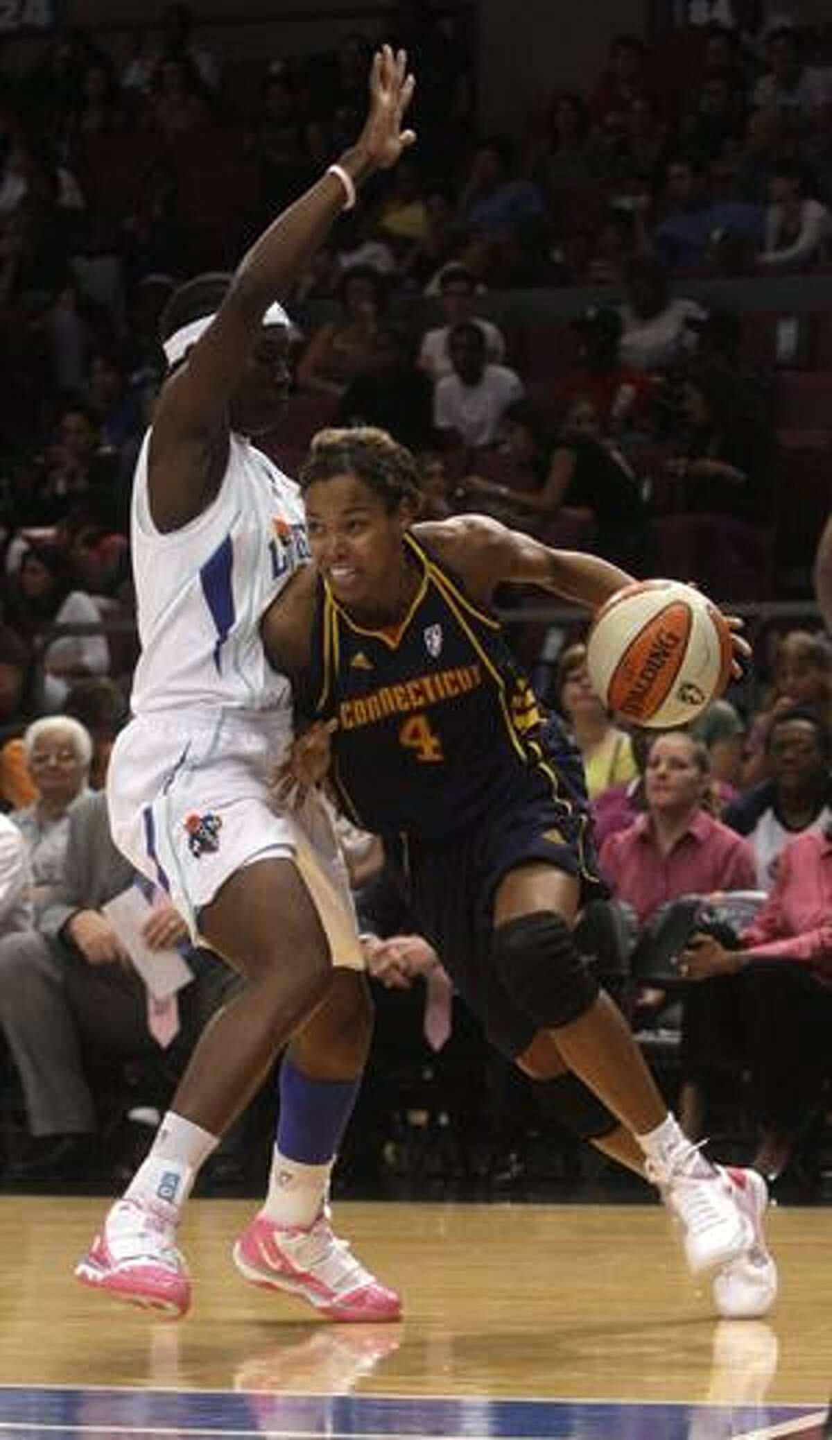 Connecticut Sun's Kiesha Brown (4) drives past New York Liberty's Essence Carson, left, during the first half Friday in New York.