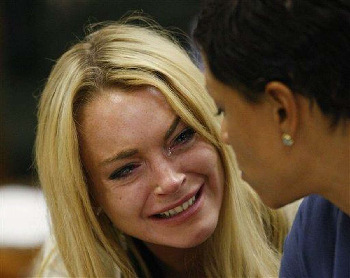 Actress Lindsay Lohan, left, reacts with her attorney Shawn Chapman Holley after the sentencing by Superior Court Judge Marsha Reve during a hearing in Beverly Hills, Calif., Tuesday, July 6, 2010. The judge sentenced Lindsay Lohan to 90 days in jail Tuesday after ruling she violated probation in a 2007 drug case by failing to attend court-ordered alcohol education classes. (AP Photo/David McNew, Pool)