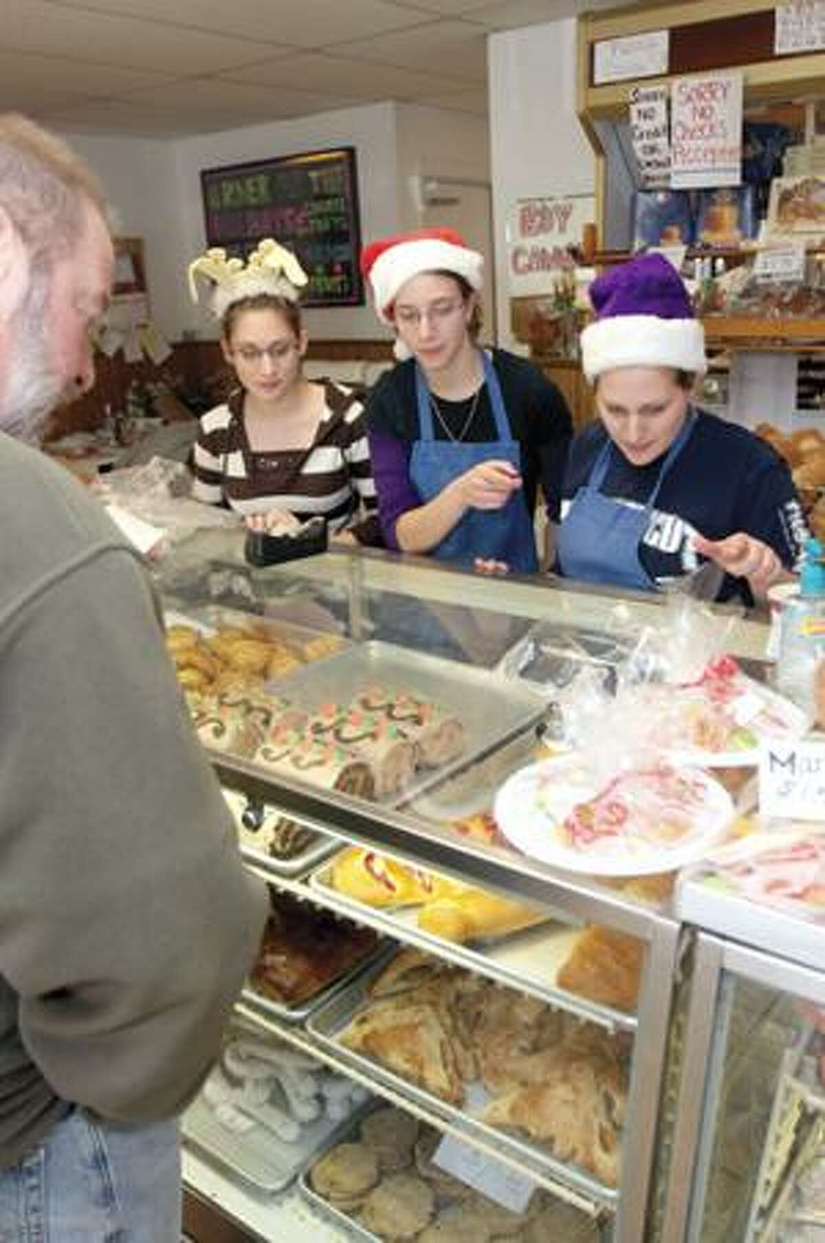 SONJA ZINKE/Register CitizenRebecca Melaragno, Erica Melaragno and Christina Tartaglino help a customer pick out a tasty delight from Lombardi's Bakery case in Torrington Thursday. Christmas Eve is typically the busiest day of the year for the bakery. Purchase a glossy print of this photo and more at www.registercitizen.com