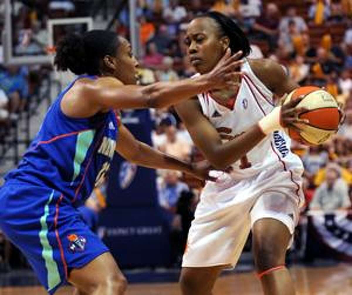 AP Connecticut Sun's Amber Holt, right, brings the ball past New York Liberty's Loree Moore during the first half of a game in Uncasville Wednesday.