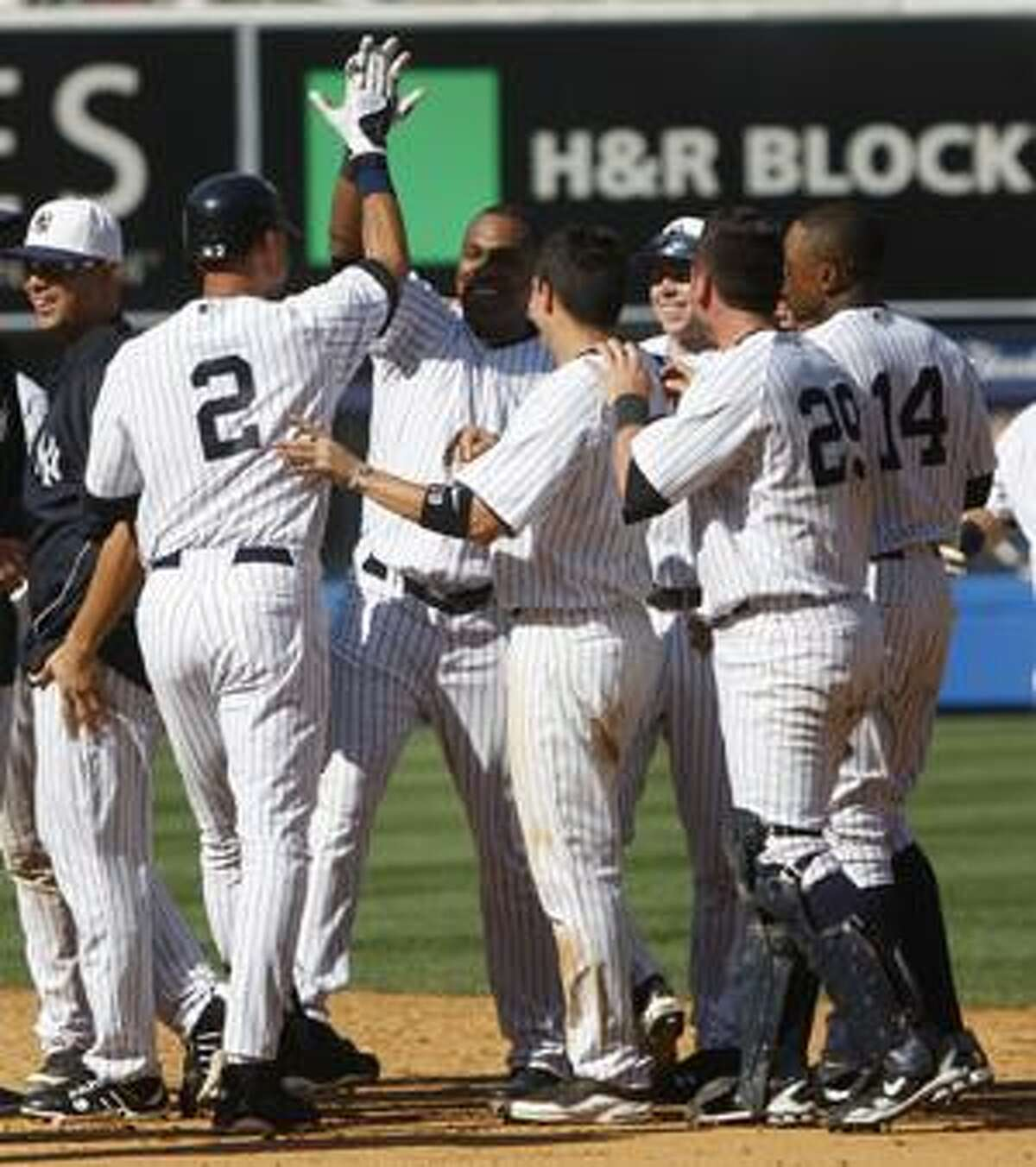 New York Yankees' Marcus Thames, third from left, is greeted by teammate Derek Jeter, second from left, after hitting a single to drive in the winning run during the tenth inning of the baseball game against the Toronto Blue Jays, Sunday, July 4, 2010, at Yankee Stadium in New York. (AP Photo/Seth Wenig)