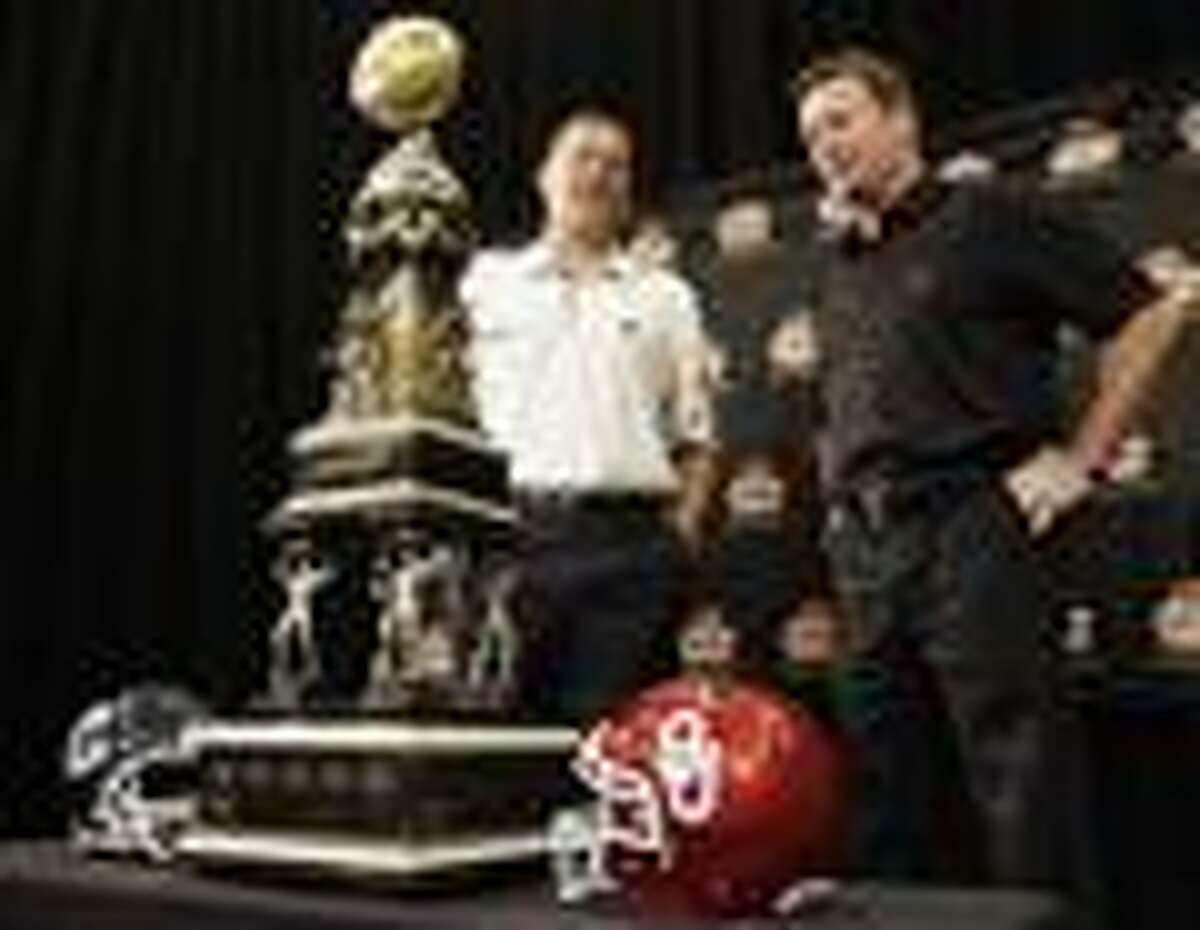 Connecticut coach Randy Edsall, left, and Oklahoma coach Bob Stoops, right, pose with the Fiesta Bowl championship trophy during a news conference Friday, Dec. 31, 2010, in Scottsdale, Ariz. The teams will face one another in the Fiesta Bowl Jan. 1. (AP Photo/Paul Connors)