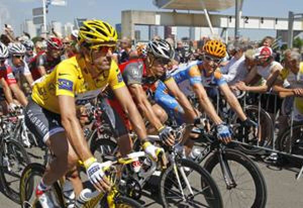 Fabian Cancellara of Switzerland, wearing the overall leader's yellow jersey, Lance Armstrong of the US, and Christian Vandevelde of the US, left to right, ride during the parade of the first stage of the Tour de France cycling race over 223,5 kilometers (139 miles) with start in Rotterdam, Netherlands and finish in Brussels, Belgium, Sunday July 4, 2010. (AP Photo/Bas Czerwinski)