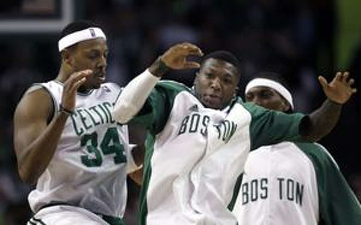 Boston Celtics forward Paul Pierce (34) celebrates with Nate Robinson, center, during a timeout in the fourth quarter against the Miami Heat in Game 5 of a first-round NBA basketball playoff series in Boston on Tuesday, April 27, 2010. The Celtics won 96-86, and took the series. (AP Photo/Elise Amendola)