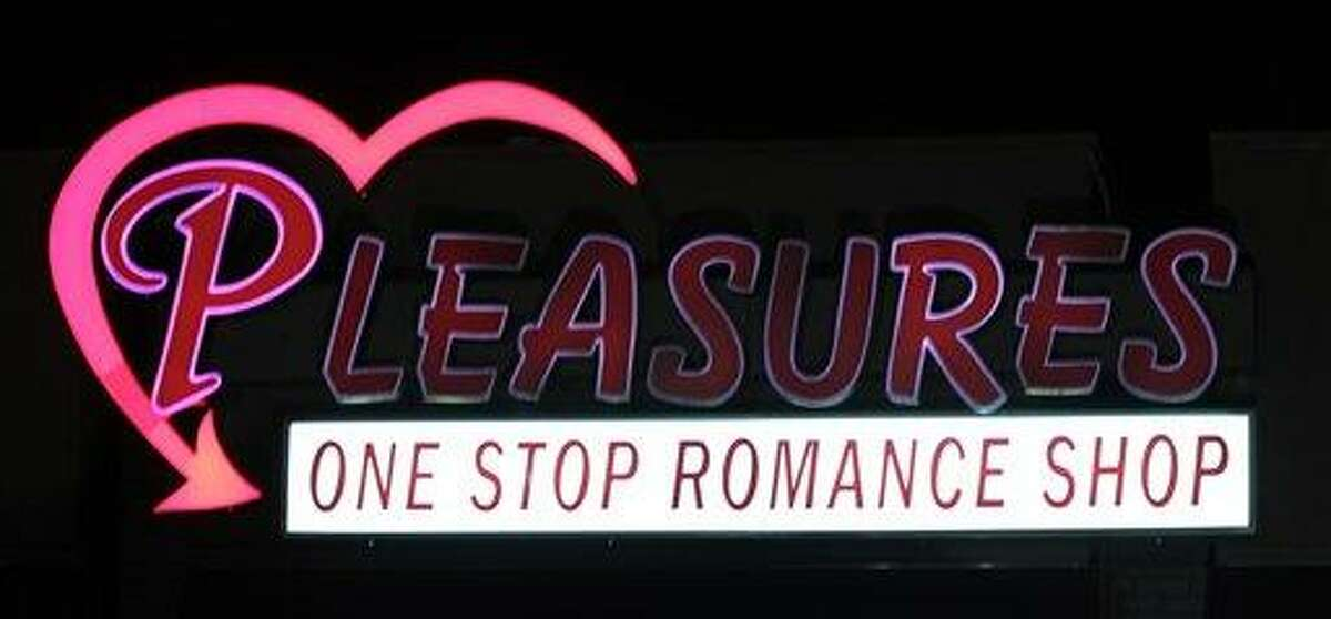 The Pleasures sign flickers over the old bank building in Huntsville, Ala., Saturday, Dec.18, 2010. The