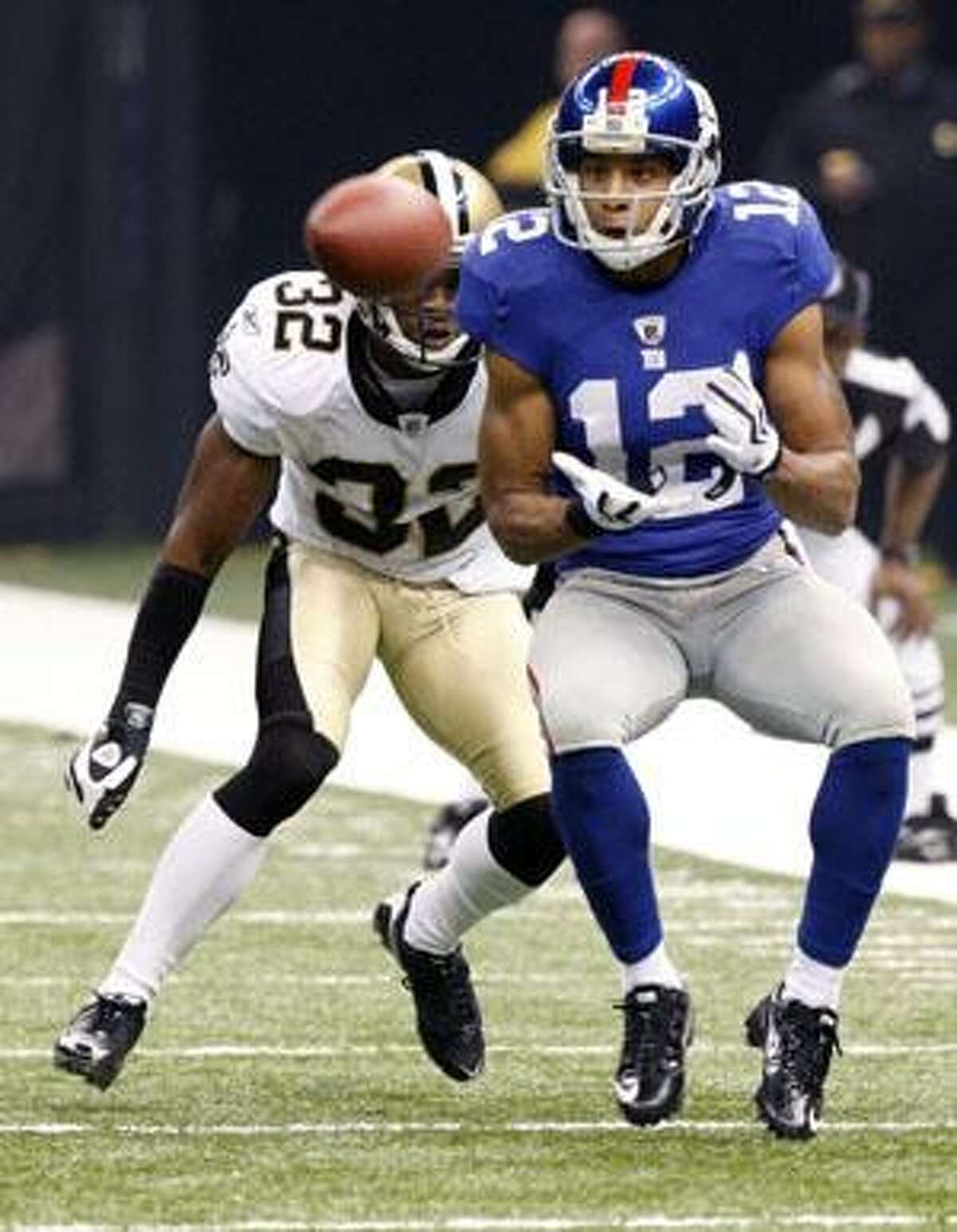 In this Oct. 18 file photo, New York Giants wide receiver Steve Smith (12) catches a pass in front of New Orleans Saints cornerback Jabari Greer (32) in New Orleans. Carolina Panthers' Dwayne Jarrett has played with both Steve Smiths. He distinguishes between the two by calling the Panthers receiver