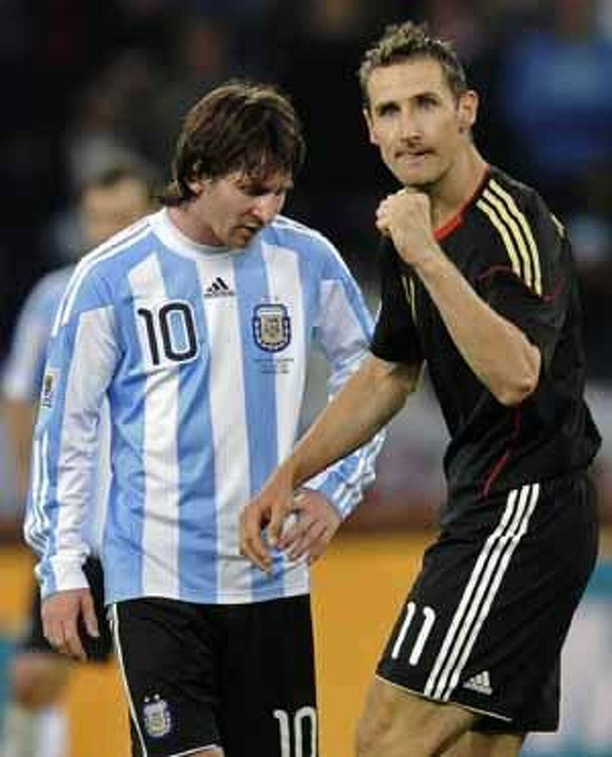Germany's Miroslav Klose, right, walks past Argentina's Lionel Messi as he celebrates after scoring his team's fourth goal during the World Cup quarterfinal soccer match between Argentina and Germany at the Green Point stadium in Cape Town, South Africa, Saturday, July 3, 2010. Germany won 4-0. (AP Photo/Martin Meissner)