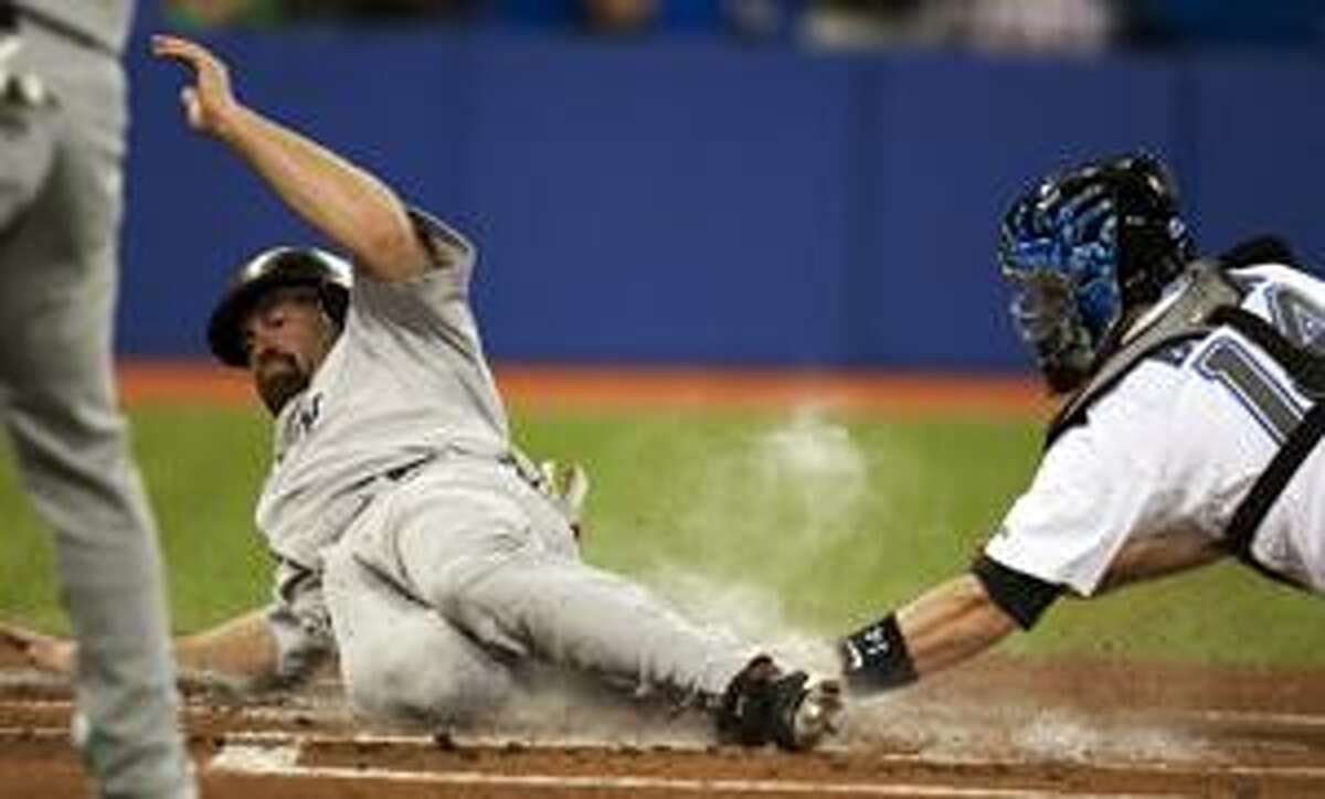 Toronto Blue Jays catcher John Buck, right, tags out Boston Red Sox's Kevin Youkilis at home plate during the first inning of a baseball game on Monday April 26, 2010, in Toronto. (AP Photo/The Canadian Press, Frank Gunn)