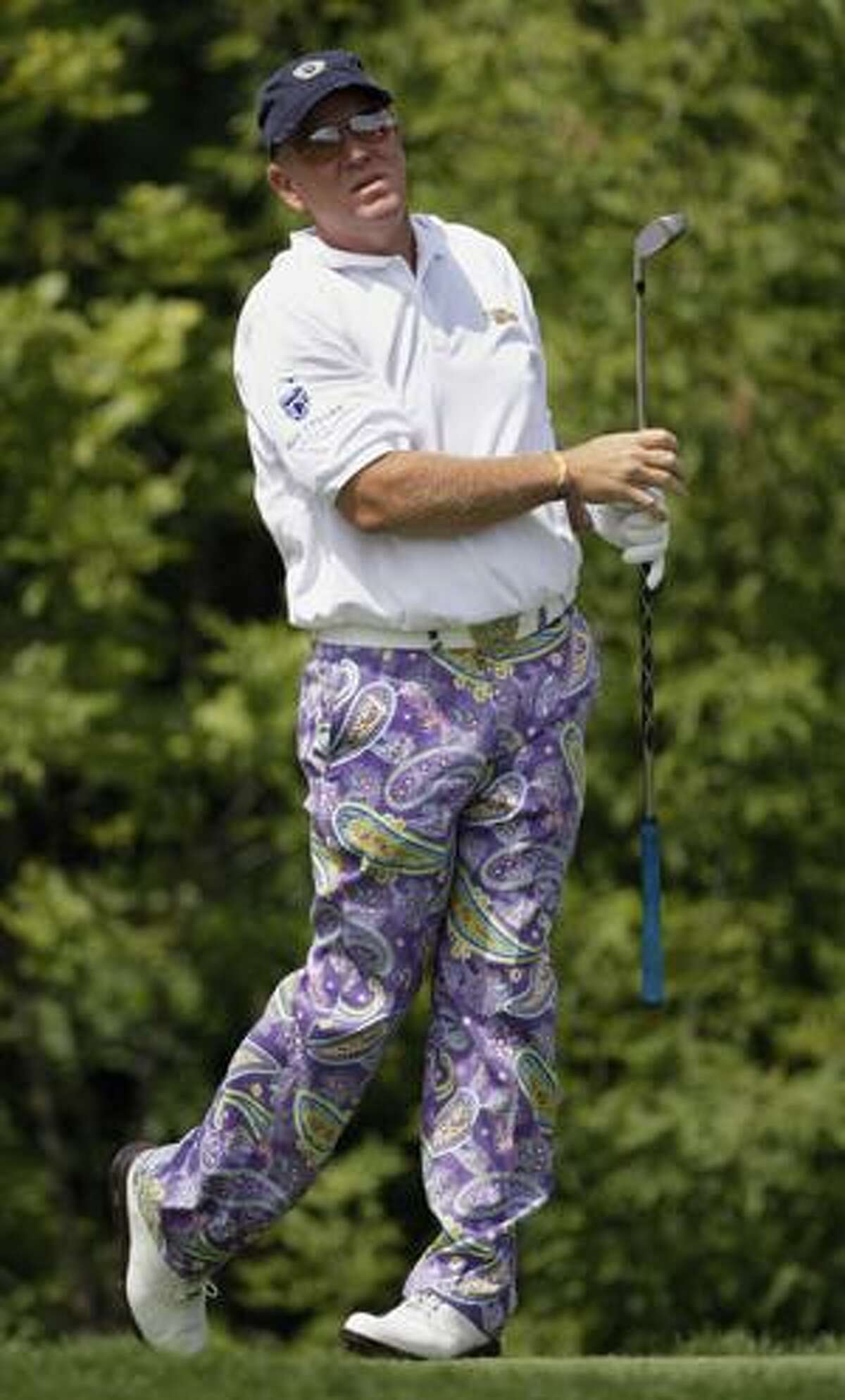 AP John Daly watches his tee shot on the 10th hole during the first round of the 91st PGA Championship at the Hazeltine National Golf Club in Chaska, Minn., Thursday. It was announced Tuesday that Daly will return to the Australian Open a year after a smashing a fan's camera into a tree during the tournament.