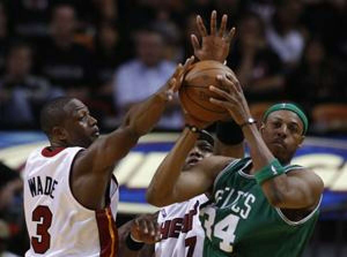 Miami Heat players Dwyane Wade (3) and Jermaine O'Neal (7) apply pressure as Boston Celtics Paul Pierce (34) looks for a shot in the second half during Game 3 in the first round of their NBA basketball playoff series in Miami, Friday, April 23, 2010. The Celtics won 100-98. (AP Photo/J Pat Carter)