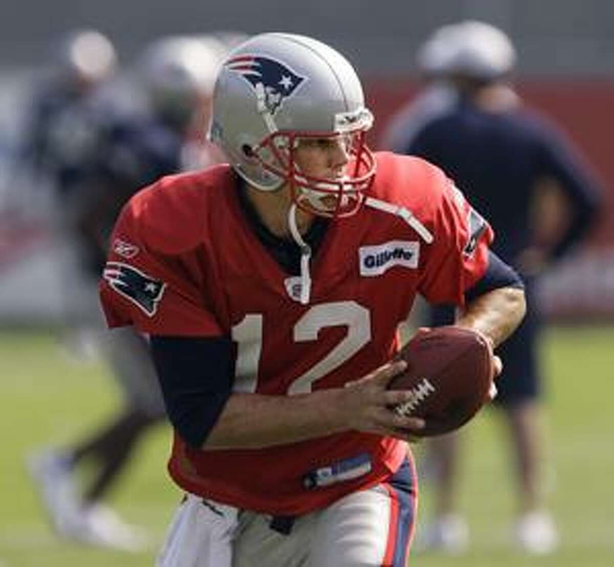 New England Patriots quarterback Tom Brady sets up to hand off the ball during the morning practice session of NFL football training camp in Foxborough, Mass., Monday, Aug. 17, 2009. (AP Photo/Stephan Savoia)
