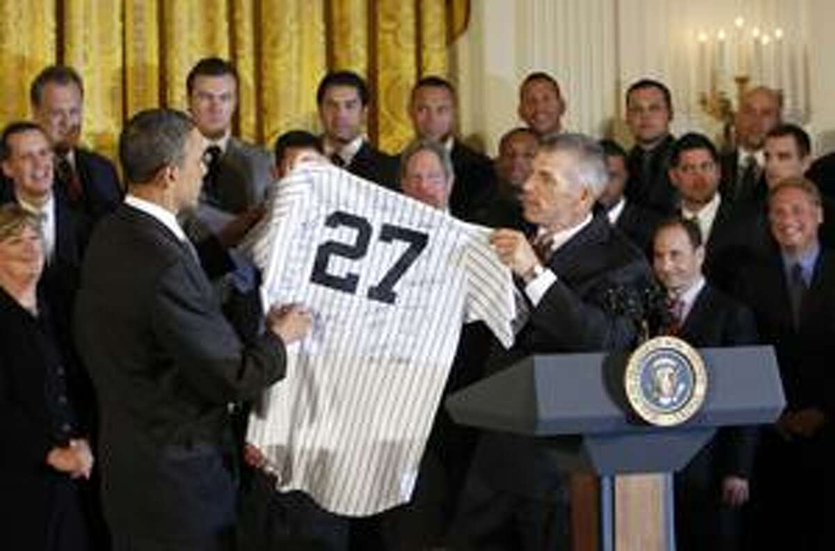 President Barack Obama, left, holds up a New York Yankees baseball team jersey, presented to him by manager Joe Girardi, right, as he honored the 2009 World Series champions New York Yankees baseball team, Monday, April 26, 2010, in the East Room of the White House in Washington. (AP Photo/Pablo Martinez Monsivais)