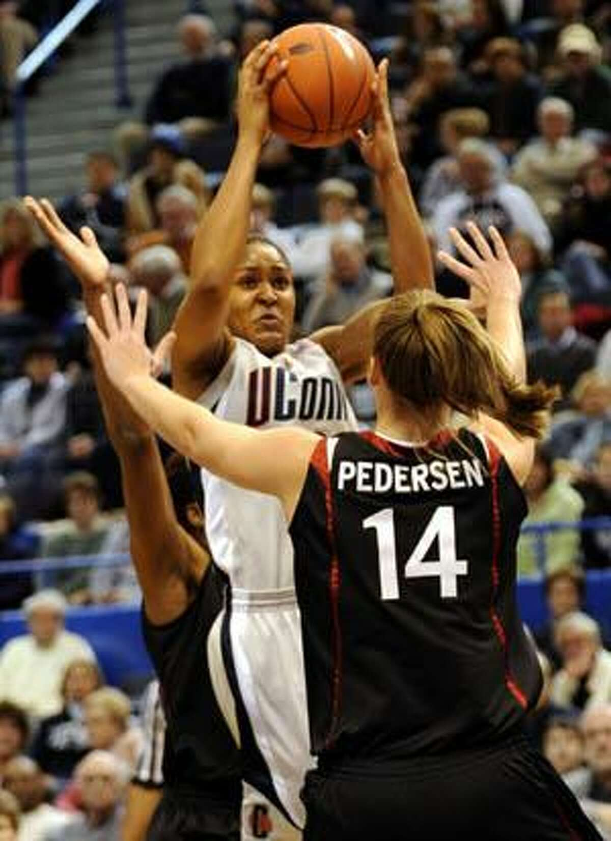 Stanford's Kayla Pedersen defends as Connecticut's Maya Moore shoots during the first half Wednesday in Hartford.