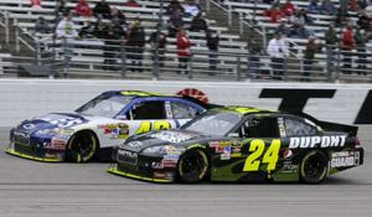 Jimmie Johnson, left, challenges Jeff Gordon (24) for the lead coming out of turn four late in the NASCAR Sprint Cup Samsung Mobile 500 auto race Monday, April 19, 2010, in Fort Worth, Texas. Denny Hamlin won the race. (AP Photo/Larry Papke)