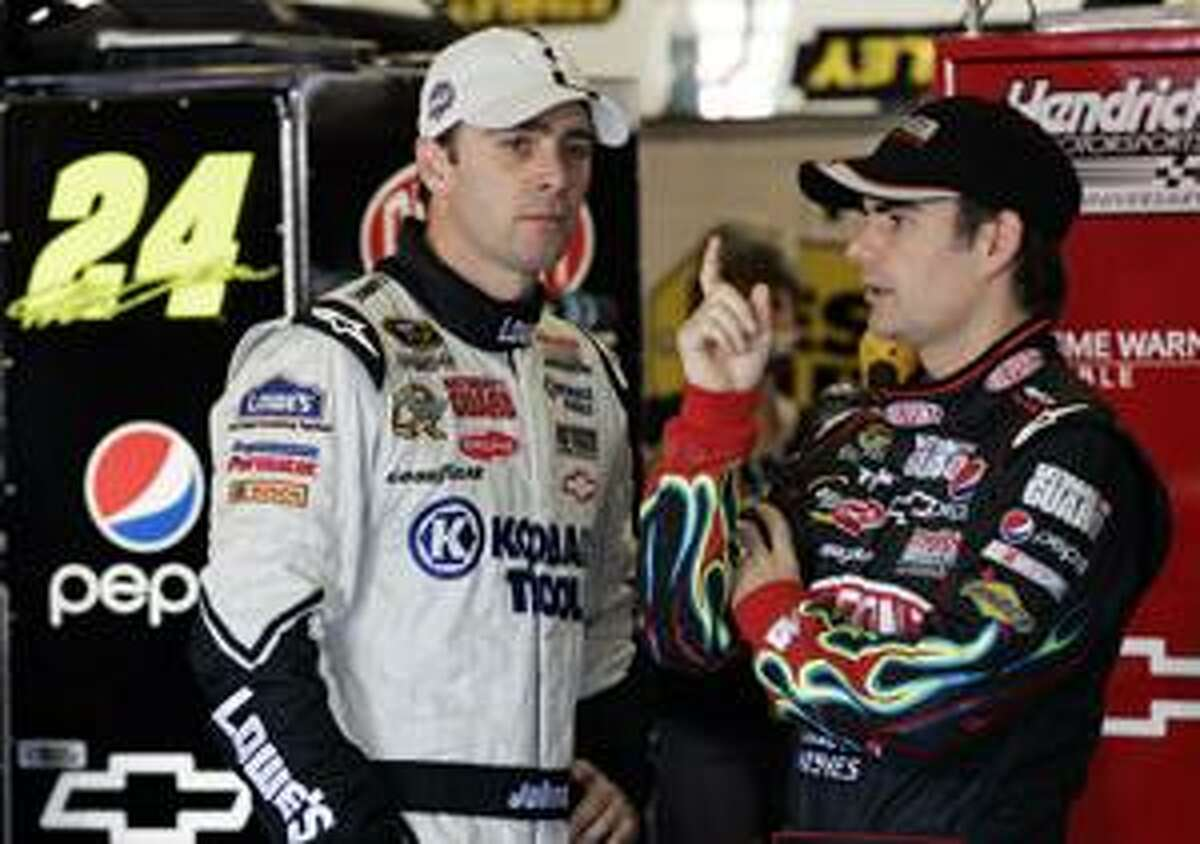 FILE - This Nov. 6, 2009, file photo shows Jimmie Johnson, left, and Jeff Gordon talking during a break in a NASCAR Sprint Cup Series practice at Texas Motor Speedway in Fort Worth, Texas. For at least a decade, Jeff Gordon was NASCAR's biggest star, winning four championships while transforming the sport on and off the track. The spotlight shifted four years ago when Hendrick Motorsports teammate Jimmie Johnson began his run. (AP Photo/Ralph Lauer, File)