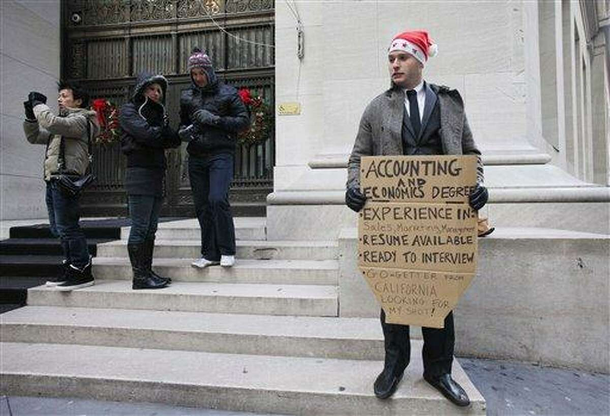In this Dec. 15, 2010 photo, Jesse Paloger holds up a sign while standing on Wall Street as he hopes to find a job, in New York. Paloger, who has an accounting and economics degree from the University of California, Santa Barbara, has written on the bottom of his sign,