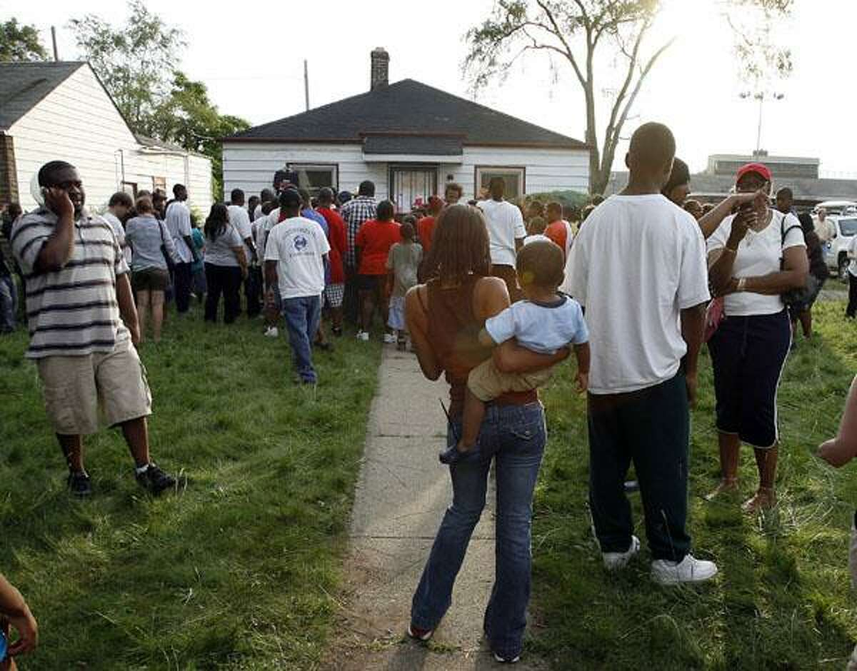 In this June 25, 2009 photo, fans and visitors stand in front of the childhood home of pop star Michael Jackson in Gary, Ind. (AP photo by John Smierciak)