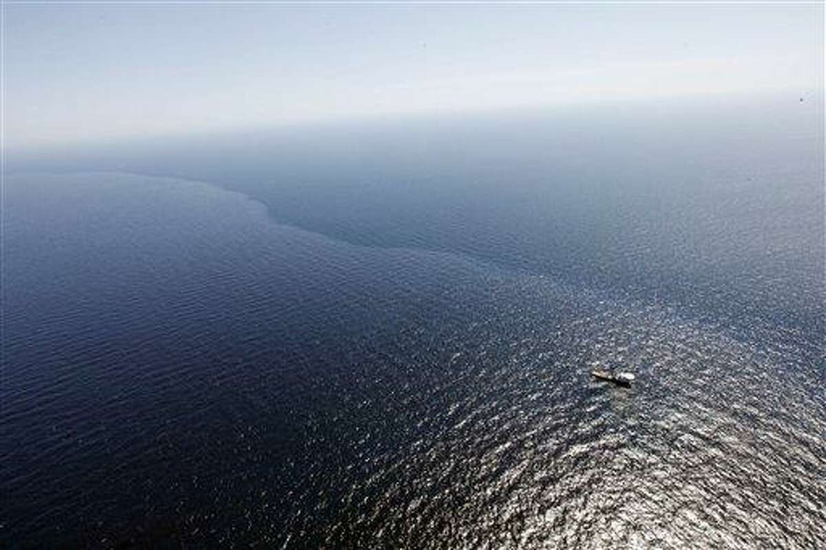 In this aerial photo taken over the Gulf of Mexico, a boat and crew work in oil which leaked from a pipeline at the Deepwater Horizon oil rig off the coast of Louisiana, Monday, April 26, 2010. Officials say there will be no shoreline impact from an oil leak in the Gulf of Mexico for at least another three days. Crews were ramping up Monday to protect the coastline after the oil rig exploded off the Louisiana coast nearly a week ago. (AP Photo/Gerald Herbert)