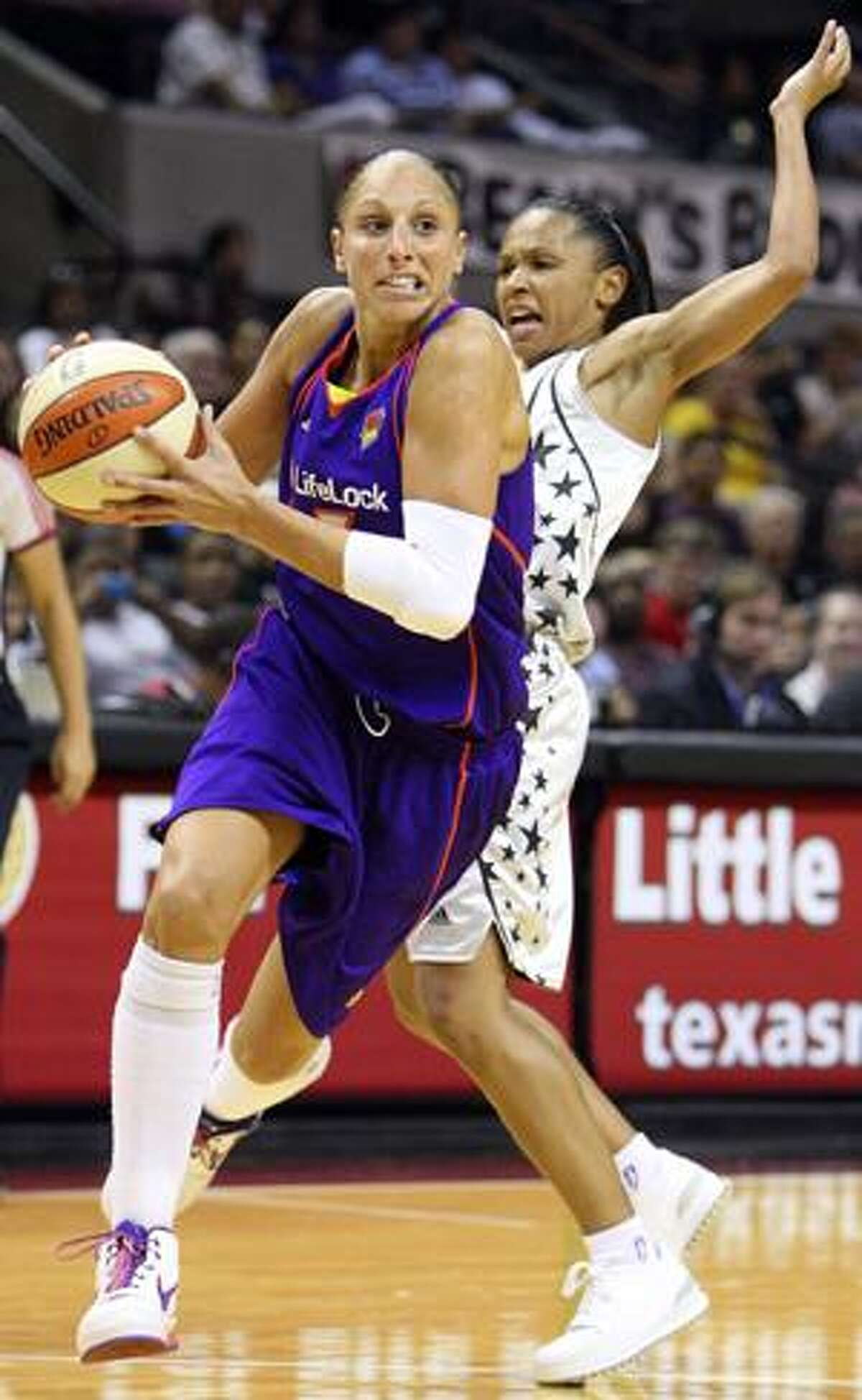 AP Phoenix Mercury's Diana Taurasi drives around San Antonio Silver Stars' Edwige Lawson-Wade during first half action in a WNBA game in San Antonio, Saturday at the AT&T Center.