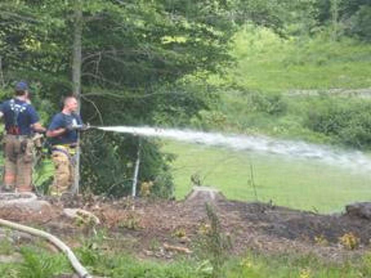 Torrington firefighters battle a brush fire on Pumping Station Road Friday.
