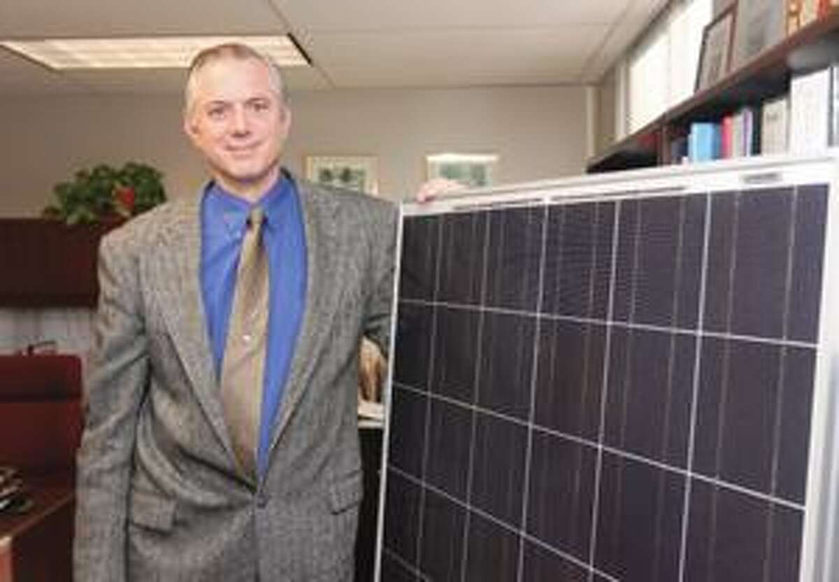 SONJA ZINKE/Register Citizen Superintendant of Schools for Regional School District 7, Clint Montgomery stands with one of the 2,000 solar panels that were installed at the school. Purchase a glossy print of this photo and more at www.registercitizen.com