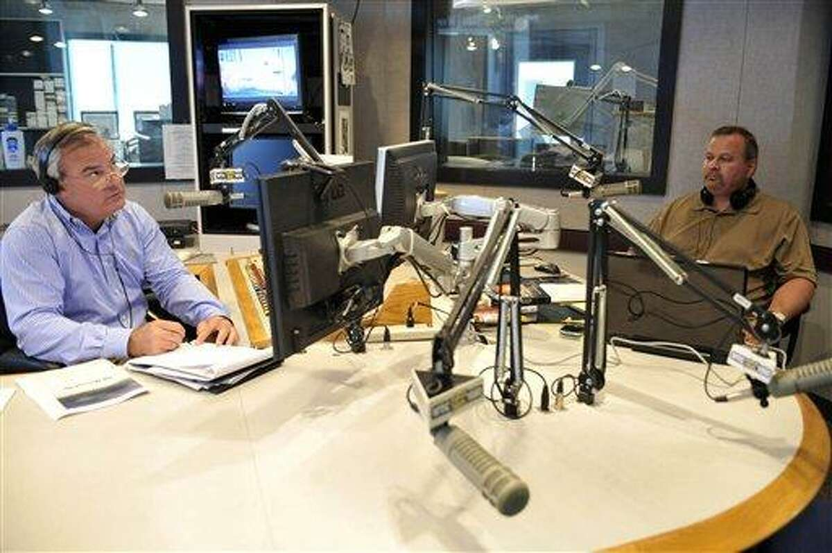 Former Connecticut Gov. John Rowland, left, fills in as a talk show host on WTIC AM radio with Pastor Will Marotti, right, in Farmington, Conn., Friday, July 2, 2010. (AP Photo/Jessica Hill)