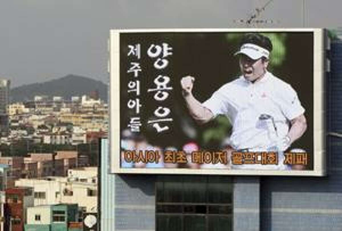 AP A huge screen shows a photo of South Korean golfer Y.E. Yang reacting to winning the 91st PGA Championship, in Jeju, south of Seoul, South Korea, Monday. Yang, ranked 110th, made history Sunday by coming from behind to beat world No. 1 Tiger Woods and become the first Asian-born man to win a major tournament, a stunning rise for the self-taught son of a farmer who first picked up a golf club at age 19. The letters read