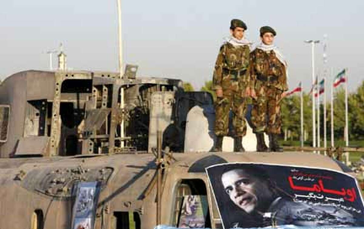 Two members of paramilitary Basij forces, affiliated to the Iranian Revolutionary Guard, stand on an abandoned US helicopter, and above a poster of US President Barack Obama, at the Azadai (Freedom) Sq. in Tehran, Iran, Sunday, during a ceremony marking failed 1980 US rescue mission to free 52 Americans held hostage at the U.S. Embassy in Tehran. AP