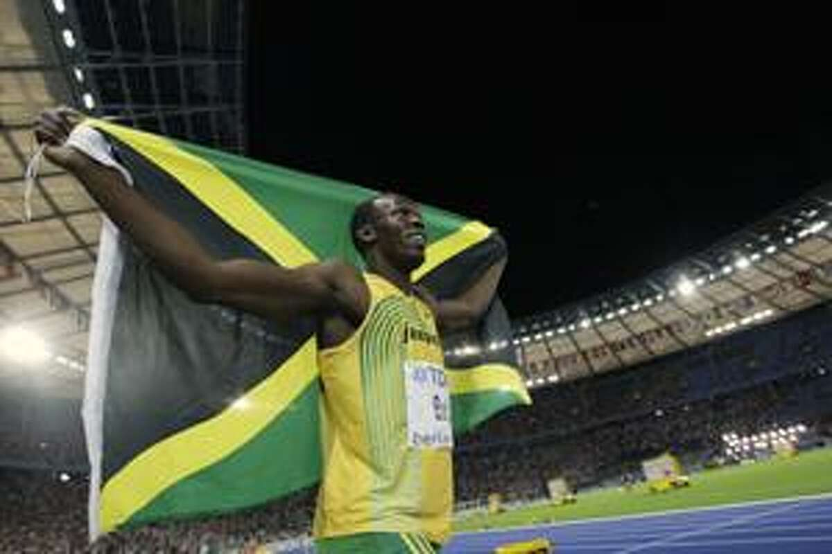 AP Jamaica's Usain Bolt celebrates with his country's flag after setting a new world record in the final of the men's 100 meters during the World Athletics Championships in Berlin on Sunday.