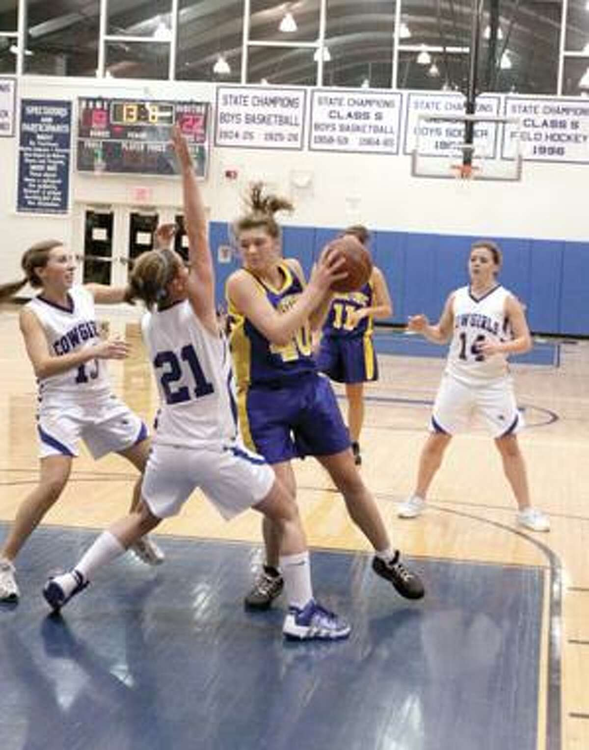 Housatonic's Danielle Kearns, center, grabs a rebound and looks to pass as Litchfield's Emily Andrulis (21) tries to block the move Monday in Litchfield.