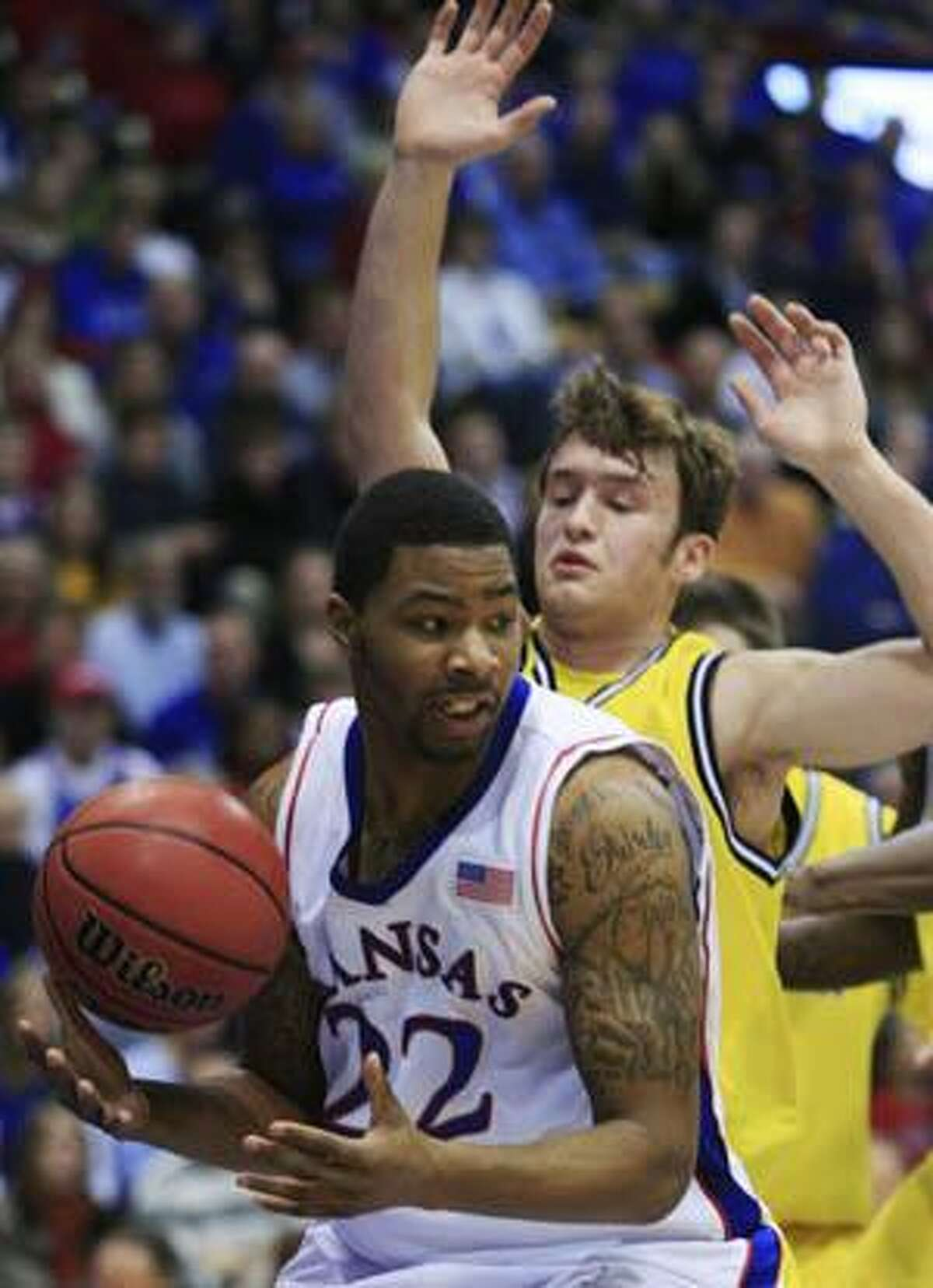 Kansas forward Marcus Morris (22) is defended by Michigan guard Zack Novak during the first half Saturday in Lawrence, Kan. Morris scored 23 points to lead Kansas to a 75-64 win over Michigan.
