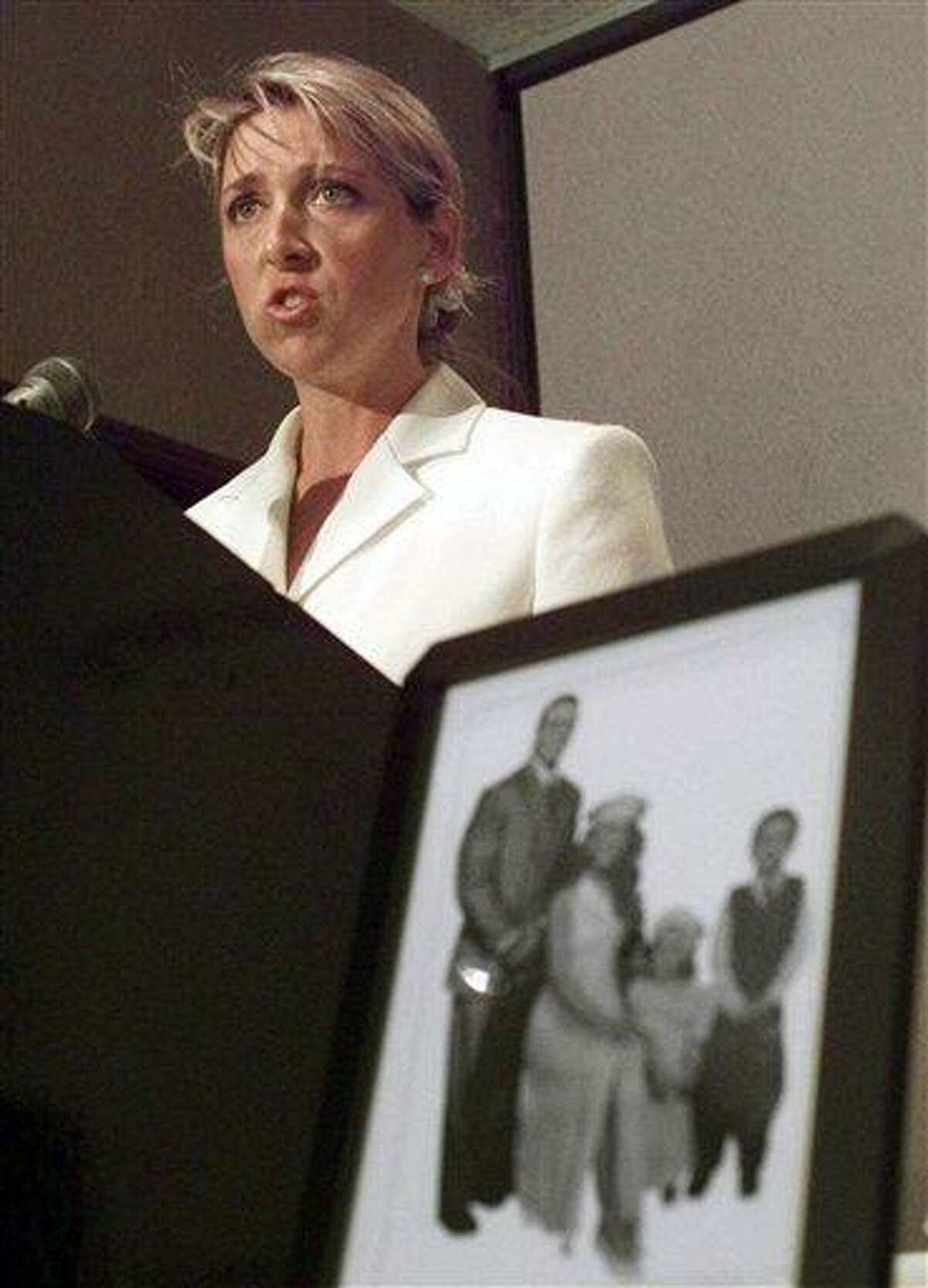 FILE - In this June 15, 1999 file photo, Martha Hart, widow of the late professional wrestler Owen Hart, announces that her family has filed a wrongful death lawsuit against the World Wrestling Federation in Kansas City, Mo., as a photo of the Harts and their two children sits in the foreground. Hart says she's suing the Connecticut-based World Wrestling Entertainment and its leaders, including Republican U.S. Senate candidate Linda McMahon, because they kept using her husband's image to promote the business despite agreeing to stop after his death. Hart plans to file her lawsuit Tuesday, June 22, 2010, in U.S. District Court in Hartford. (AP Photo/Cliff Schiappa, File)