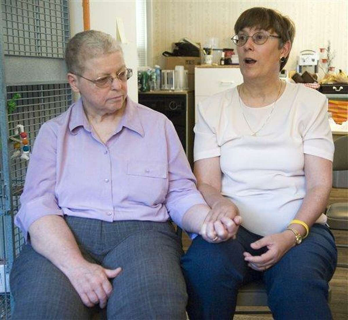 FILE - In this July 18, 2006 file photo, Margaret Mueller, left, and Charlotte Stacey hold hands during a news conference at their home in Norwalk, Conn. Mueller and Stacey sued two doctors in 2006, accusing them of treating Mueller for ovarian cancer when she actually had cancer of the appendix. They said Mueller underwent years of devastating chemotherapy treatments while the real cancer spread. A jury awarded $2.45 million to Mueller's estate Friday, July 2, 2010, to settle the malpractice case, (AP Photo/Douglas Healey, File)