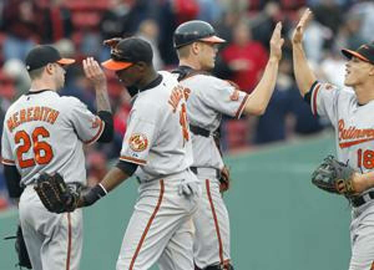 AP Baltimore Orioles', from left to right, Cla Meredith, Adam Jones, Craig Tatum and Lou Montanez celebrate their 7-6, 10-inning win against the Boston Red Sox, Sunday in Boston.