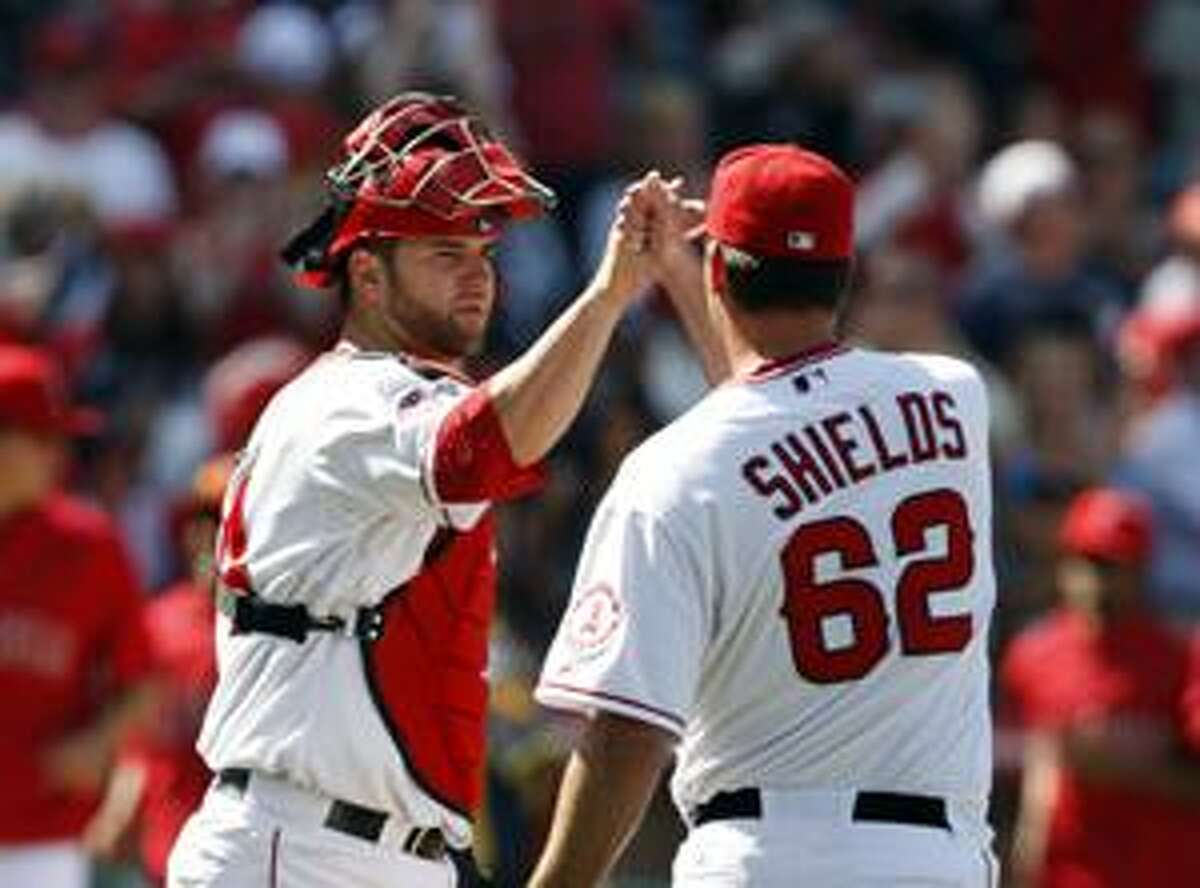 AP Los Angeles Angels pitcher Scot Shields gets congratulations from catcher Mike Napoli after an 8-4 victory against the New York Yankees, Sunday, in Anaheim, Calif.