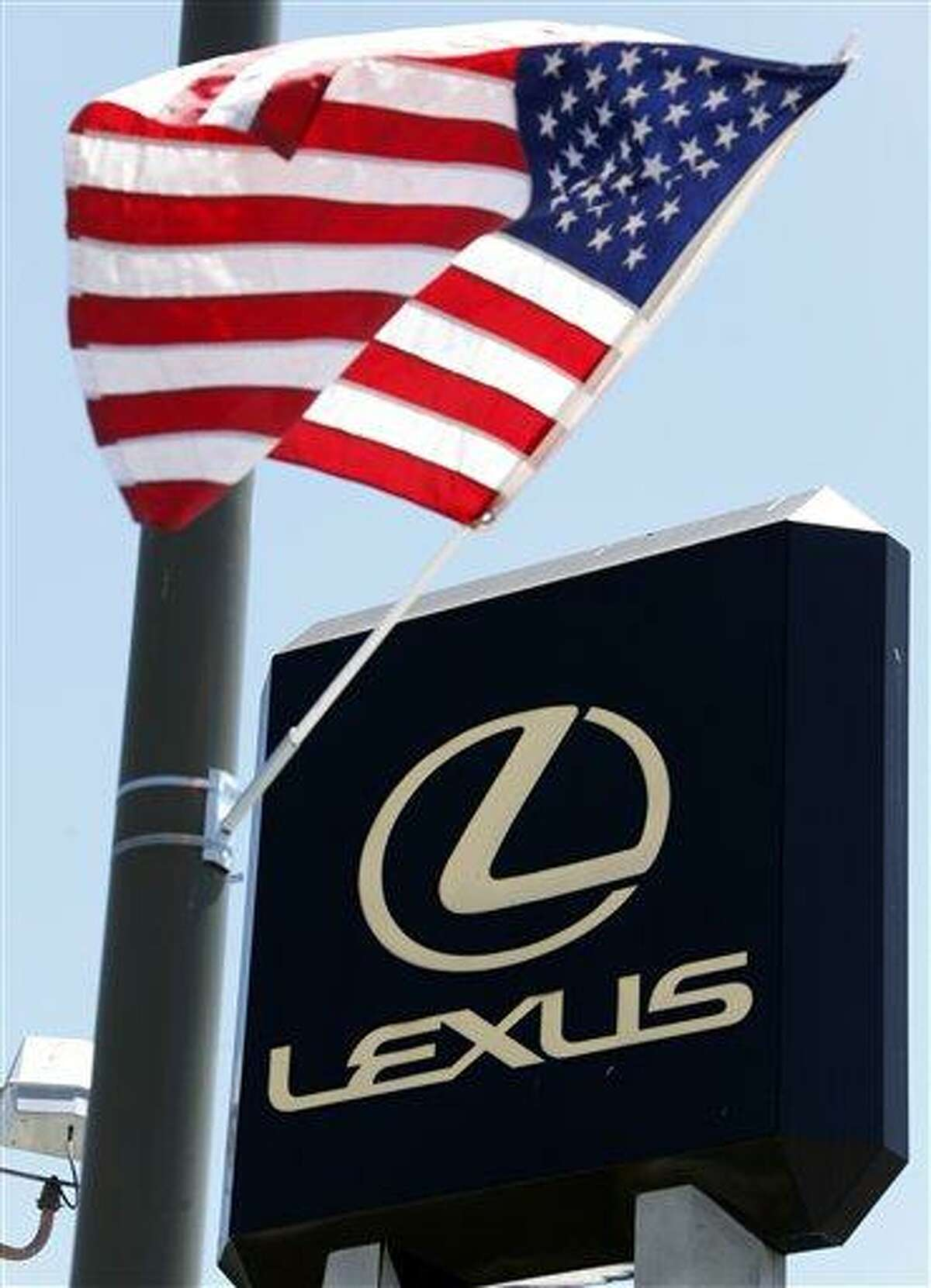 A U.S. flag is seen over a large sign at a Lexus dealership in the Woodland Hills area of Los Angeles Thursday, July 1, 2010. Toyota Motor Corp. says around 270,000 vehicles sold worldwide, including luxury Lexus sedans, have faulty engines. It did not say whether it would recall the vehicles. (AP Photo/Reed Saxon)